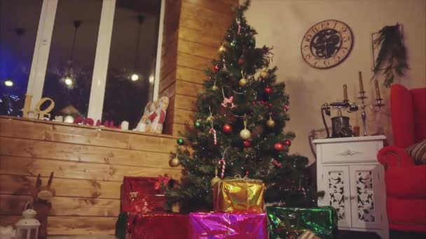 View of christmas decorated room with pine tree and presents under it