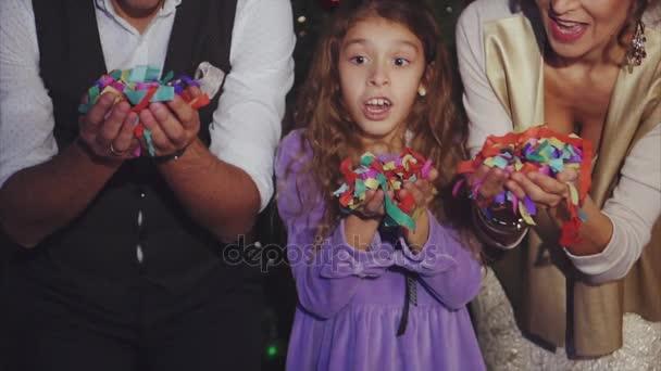 Lassú lövés boldog család fúj színes karácsonyi konfetti