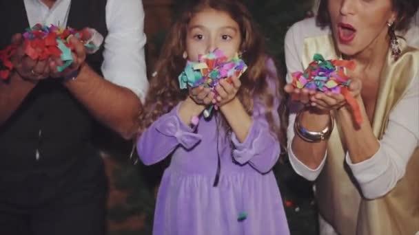 Boldog család ünnepli karácsony és újév-fúj színes konfetti
