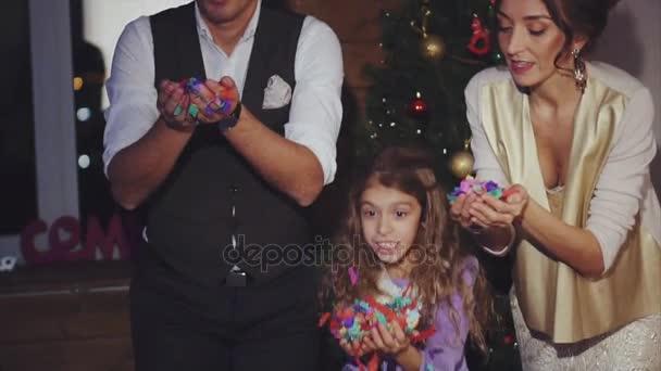 Boldog anya, apa és lánya fúj színes konfetti ünnepe a karácsony