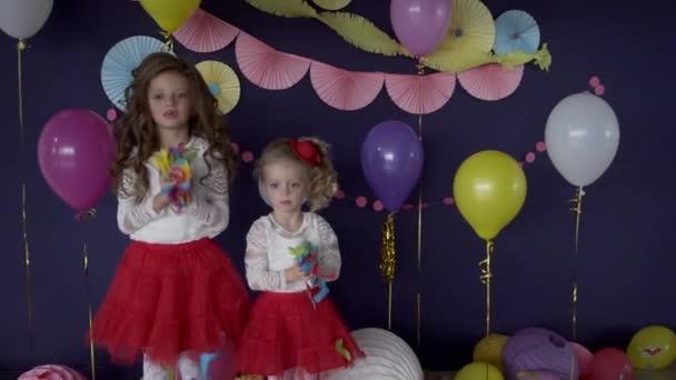 Zwei baby ziemlich Mädchen Schwestern werfen Konfetti hell und feiert Geburtstag