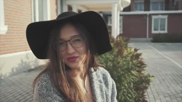 Zblízka portrétní docela usmívající se žena v černém klobouku a brýle venkovní