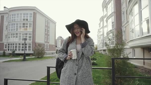Attractive business woman in hat and glasses commuter using smartphone outdoor