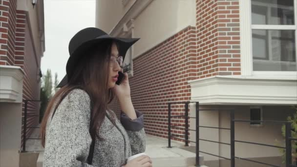 Young pretty woman in black hat and glasses talking on the phone outdoor