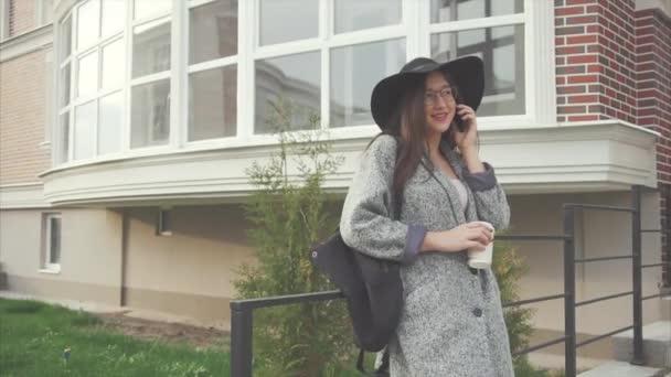 Atraktivní obchodní žena v černém klobouku a brýle mluvit na telefonu