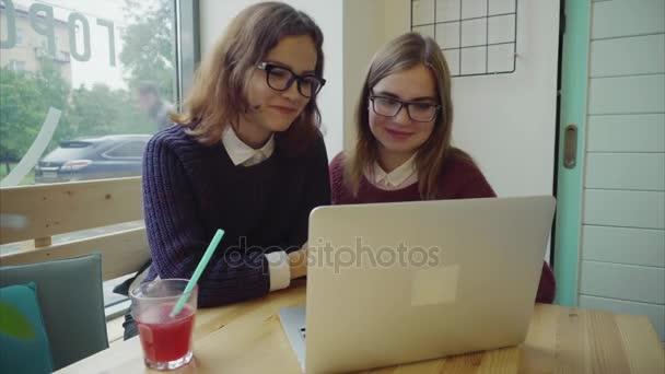 Dvě dívky mluvit s přáteli přes webchat nebo s video chat v kavárně