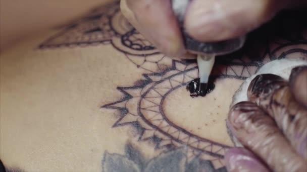 Detail z rukou tetování umělce v rukavicích tetování vzor na těle makra