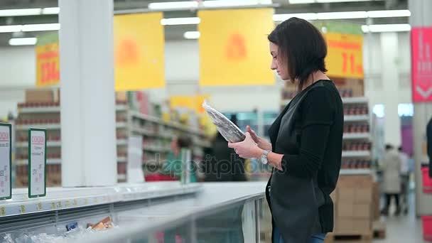 Brunetka si vybere zmrazených produktů v supermarketu