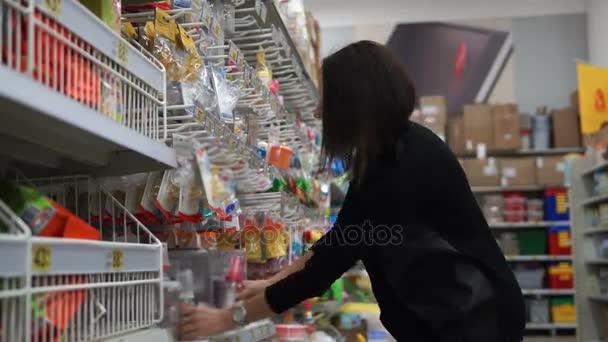 Žena matka v supermarketu si vybere malé lahvičky pro krmení dítěte