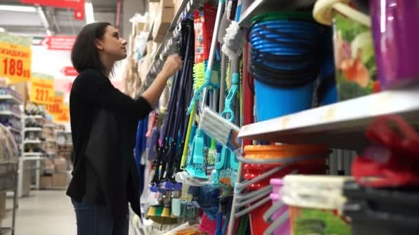 Junge Frau wählt einen Mopp für wischen