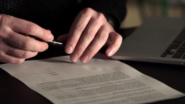 Nahaufnahme eines Mannes, der die Unterschrift auf dem Abkommen hinterlässt.