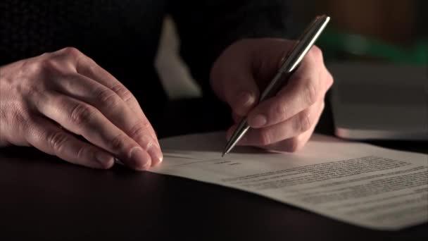 Detailní záběr záběr rukou správce, kdo podpis na dokumenty. On je levák