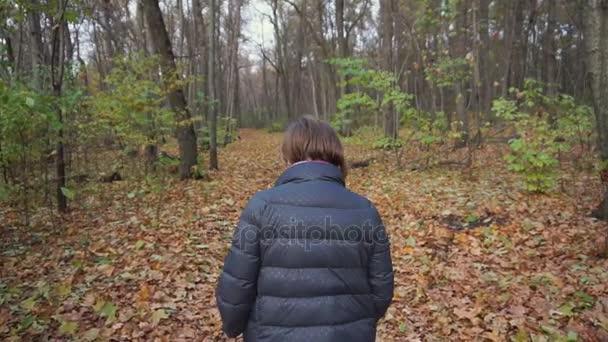 Starší žena jde na cestě podél podzimní les