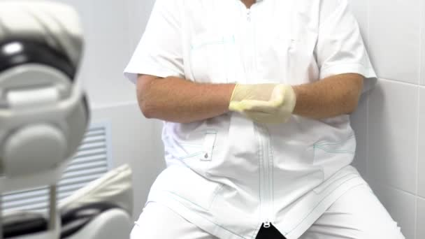 Close up shot of dentist puts gloves on his hands in dental clinic.