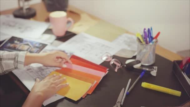 Hände der Designerin bei der Wahl der zukünftigen Möbelfarbe ihres neuen Projekts.