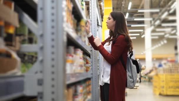 Mladá žena výběr sklenice kukuřice v hypermarketu.
