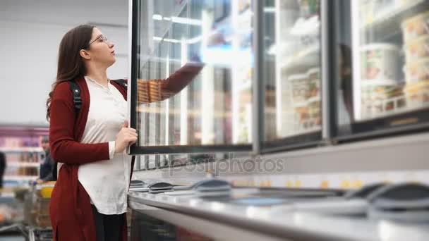 Žena s batohem vybírá produkty z chladničky v supermarketu