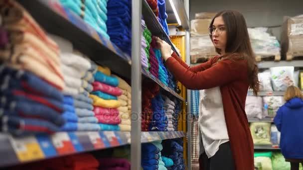 Mladá krásná žena volit mezi hnědé a modré barvy pro ručníky v koupelně