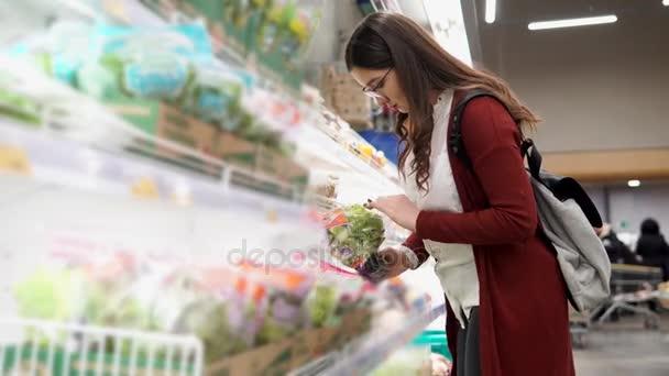 Mladá žena zvolit čerstvý salát v obchodu s potravinami.