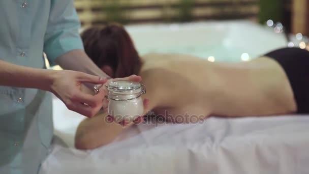 Detailní záběr záběr masáže rukou, který otevře sklenice s olejem pro lázeňské procedury
