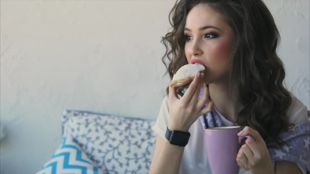 Pretty woman eating cookies and drink coffee in the bed in her bedroom.