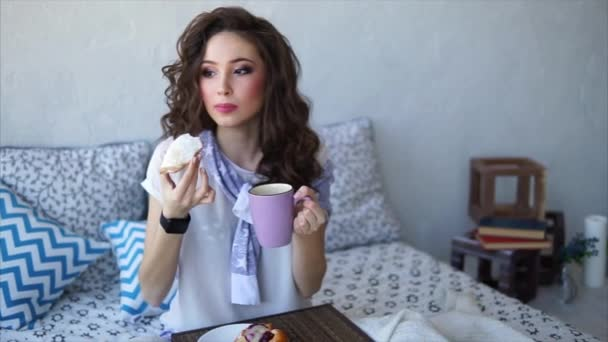 A young woman takes a bite of a cake and drinks coffee with milk in bed.
