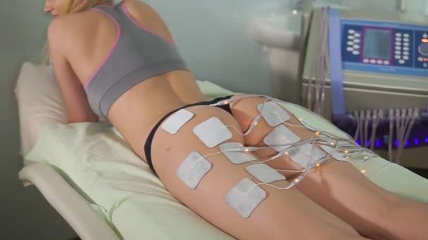 Frau bekommt Elektrostimulationstherapie am Hintern.