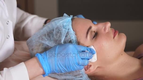 Kosmetik-Verfahren. Frau, die Gesichtsmaske von Kosmetikerin anwenden.