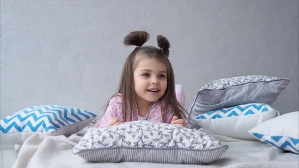 Malá holčička v posteli ležící na polštáře. Šťastné dětství