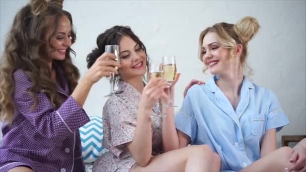 Happy and cheerful friends are happy with a pajama party and drink champagne.