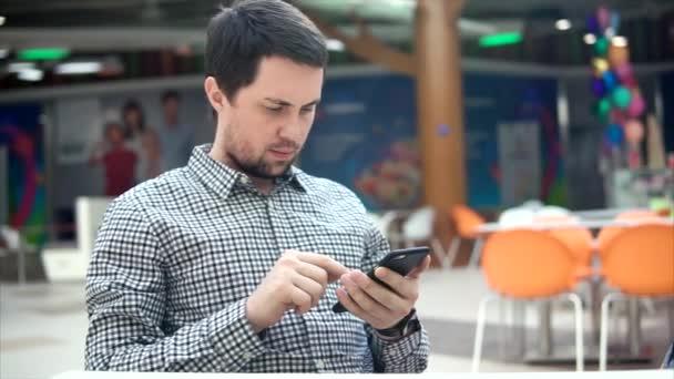 Muž s fokusem pohledem sleduje zpravodajství na internetu prostřednictvím telefonu