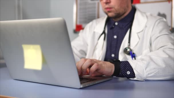 Close up shot of modern male medic in white coat using laptop.