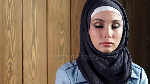 Portrait of a modern Muslim woman wearing a hijab, standing on a background