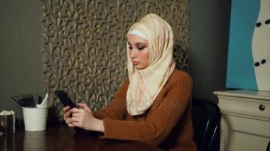 Young Muslim woman using smart phone in cafe