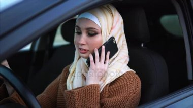 Muslim woman talking on mobile in the car
