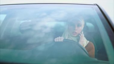 Muslim woman talking on mobile in the car, view through windscreen