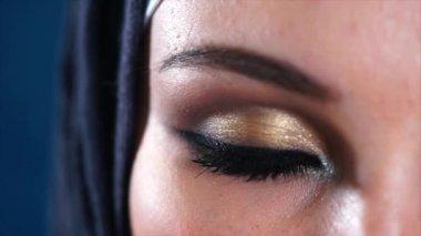 Dark brown eyes of young Muslim woman in headscarf