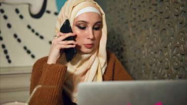 Modern Muslim woman is on cell while working with laptop in cafe