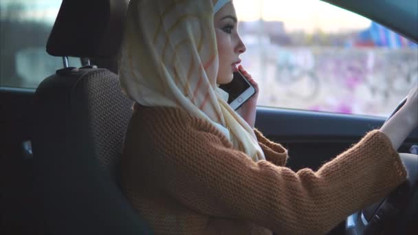 Muslim woman drives a car in the city. She uses cell phone.