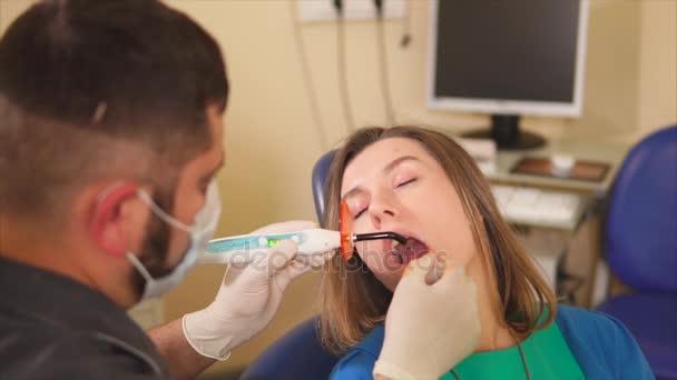 Ein männlicher Zahnarzt trocknet ein leichtes Siegel von einer Frau, die zur Zahnbehandlung kam