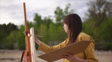 Woman artist painting en plein air
