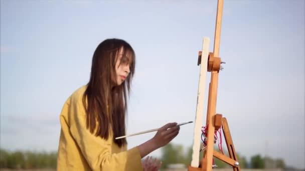 Malířka kreslení obrázek s olejovou barvou u jezera