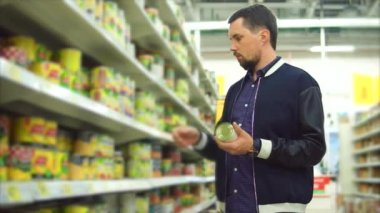 Man choosing canned vegetables in the supermarket