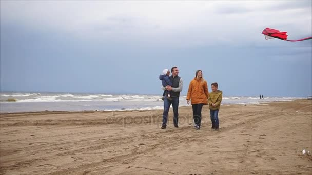 A young family walks along the beach in cold weather with a kite