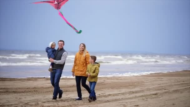 Happy family with two children enjoying a weekend with a kite on the beach