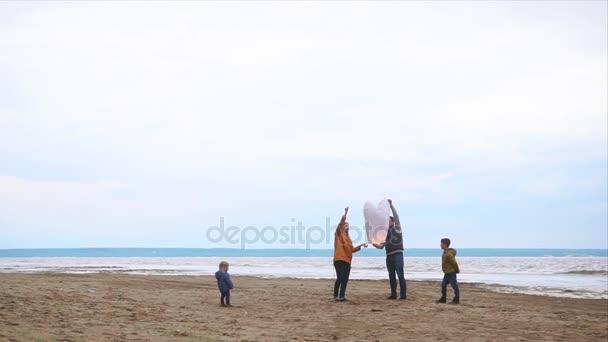 Rodiče a děti létající Lampion na pobřeží