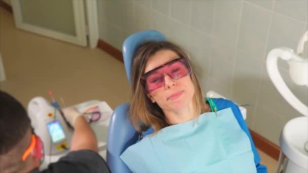 f1d007ada Paciente do sexo feminino com óculos de proteção laranja sentado no sofá  dental– gráficos de vetor