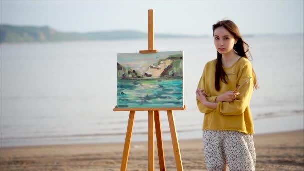 Žena umělkyně a její krajinomalby v jasném slunci venkovní