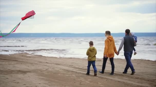 Happy family walking along the shore. Man, woman, little boy and girl playing