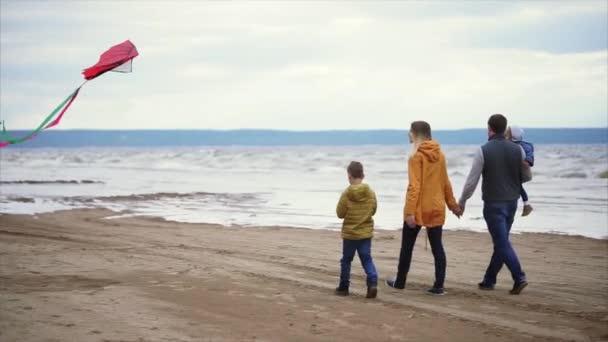 Šťastná rodina, procházky podél pobřeží. Muž, Žena, malý chlapec a dívka si hraje
